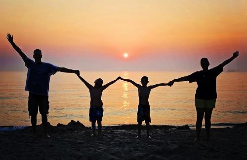 Familie bij zonsondergang op het strand